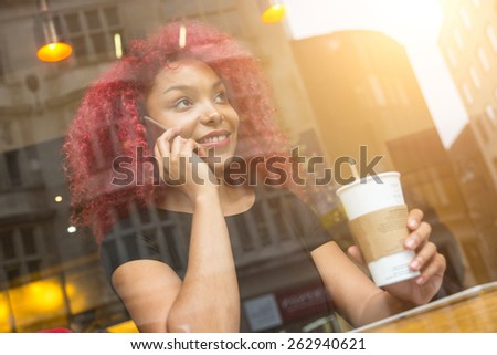 Beautiful girl with curly red hair talking on smart phone in a cafe, seen through the window with buildings reflections - stock photo