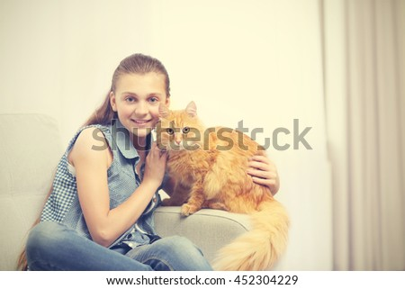 Beautiful girl with cute cat on grey couch
