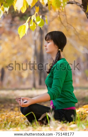 beautiful girl with dark hair, yoga in the yellow autumn leaves - stock photo
