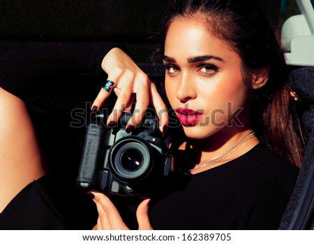 Beautiful girl with digital camera in nature. - stock photo