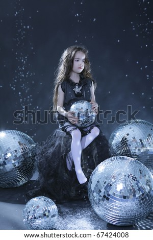 Beautiful girl with disco balls. Black background - stock photo