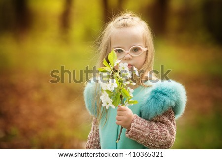 beautiful girl with down syndrome holding spring flowers - stock photo
