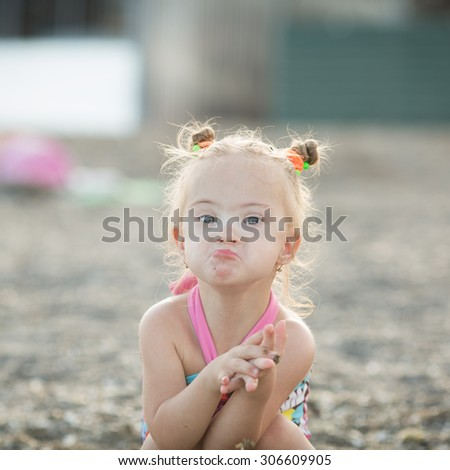 beautiful girl with Down syndrome makes a kiss - stock photo