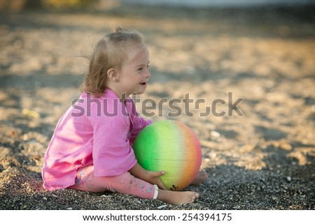 beautiful girl with Down syndrome playing with a ball on the beach - stock photo