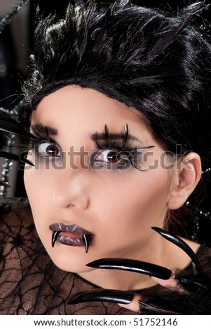 Beautiful girl with elaborate makeup posing as a spider in the web