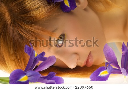 beautiful girl with face laying near some purple flower