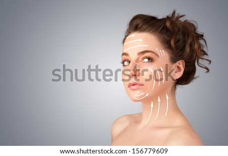 Beautiful girl with facial arrows on her skin on gradient background