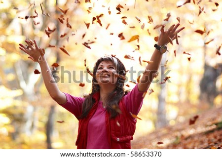 Beautiful girl with falling leaves in the autumn park - stock photo