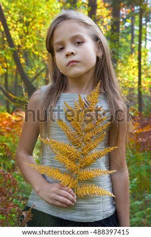 Beautiful girl with fern leaf in hand in autumn forest