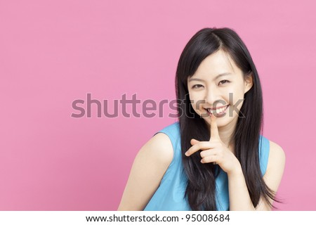 beautiful girl with finger on lips - stock photo