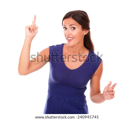 Beautiful girl with finger pointing up while looking at you in white background - copyspace - stock photo