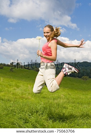 beautiful girl with flower jump on meadow - stock photo