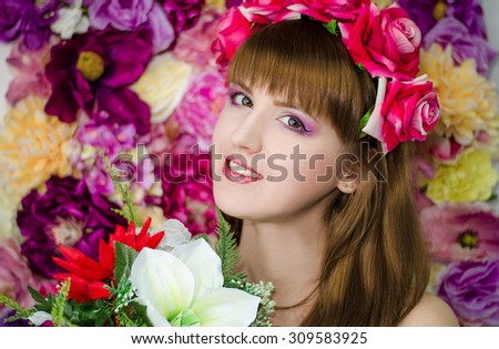 Beautiful girl with flowers. Beauty with a beautiful professional make-up. - stock photo