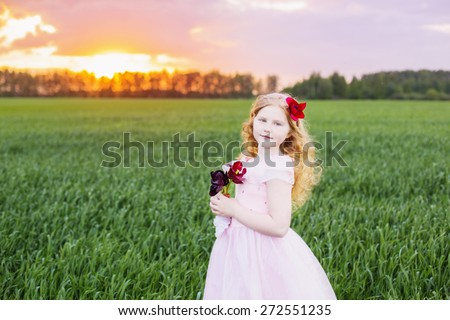beautiful girl with flowers on field - stock photo
