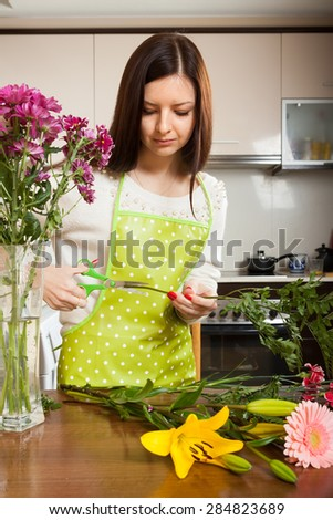 Beautiful girl with flowers on  kitchen table - stock photo