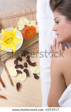 Beautiful girl with flowers relaxing on massage table - Beauty and Spa