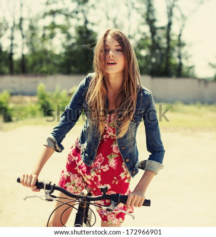 beautiful girl with flowing hair on a bicycle - stock photo