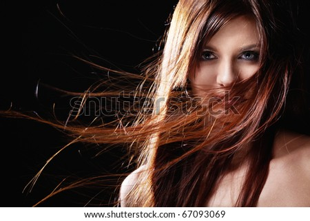 Beautiful girl with flowing hair on a black background - stock photo