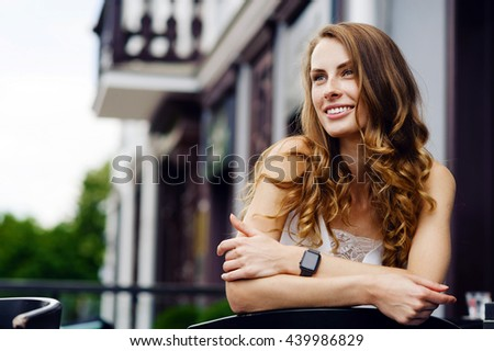 Beautiful girl with freckles and long curly hair in the street. Lifestyle outdoor portrait - stock photo