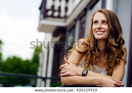Beautiful girl with freckles and long curly hair smiling in the street. Lifestyle outdoor portrait - stock photo