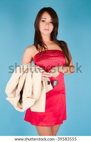 Beautiful girl with fur coat and car key - stock photo