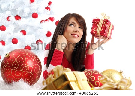 Beautiful girl with gift box next to white christmas tree - stock photo