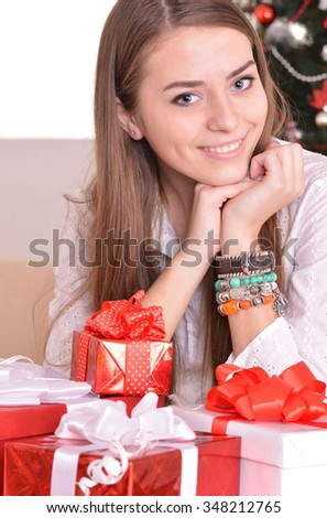 Beautiful girl with  gifts near the Christmas tree