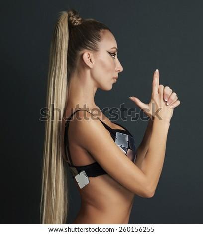 Beautiful girl with gorgeous hair making gun gesture - stock photo