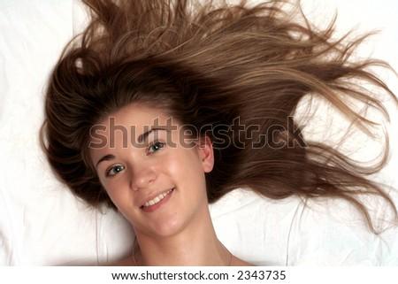 beautiful girl with green eyes lying on white bedheet - stock photo