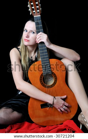 Beautiful girl with guitar, on black background - stock photo