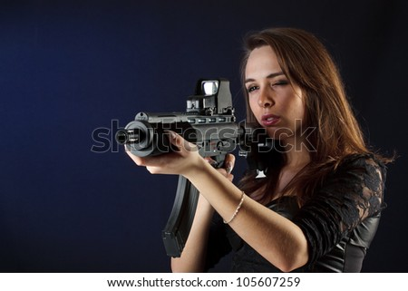 Beautiful girl with gun on blue background - stock photo