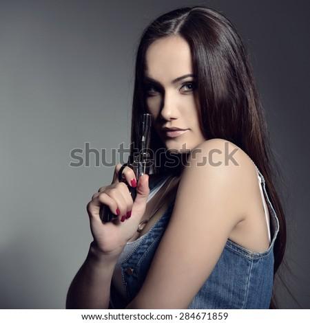 Beautiful girl with gun, studio shot. - stock photo