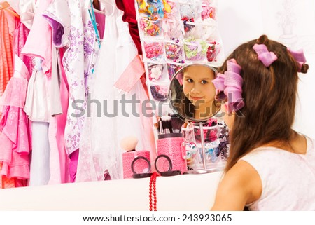 Beautiful girl with hair-curlers looks in mirror
