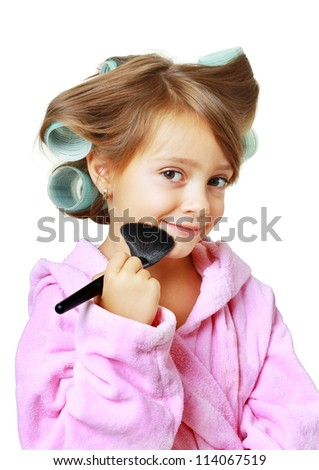 Beautiful girl with hair curlers putting on makeup, isolated on white - stock photo