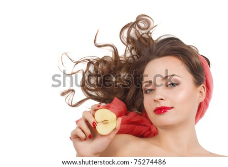 Beautiful girl with half apple lying on a white floor, a studio portrait. - stock photo