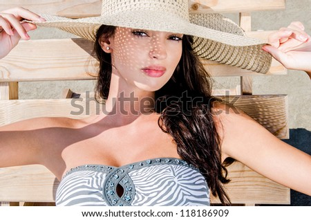Beautiful girl with hat at the beach lying on a lounge chair in summer. - stock photo