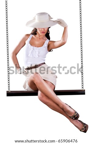 Beautiful girl with hat swinging on swing. Isolated on white