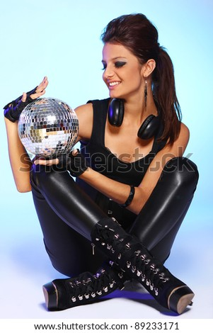 Beautiful girl with headphones and disco ball over light blue background