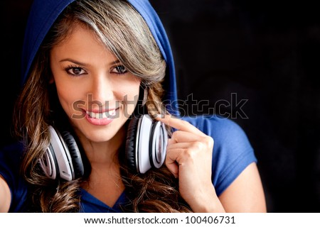Beautiful girl with headphones and wearing a hoddie - stock photo