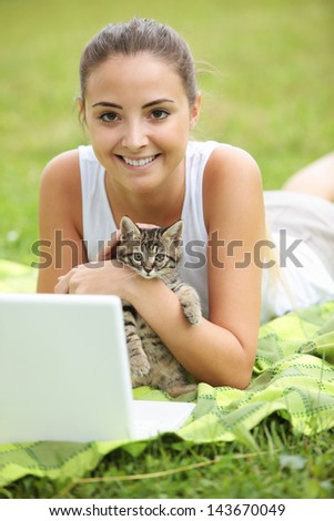 Beautiful girl with her kitty and laptop outdoors
