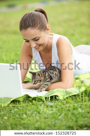 Beautiful girl with her kitty and laptop outdoors - stock photo