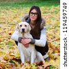Beautiful girl with labrador retriever in Autumn forest - stock photo