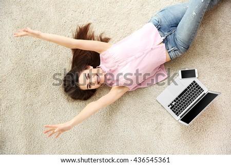 Beautiful girl with laptop lying on floor - stock photo
