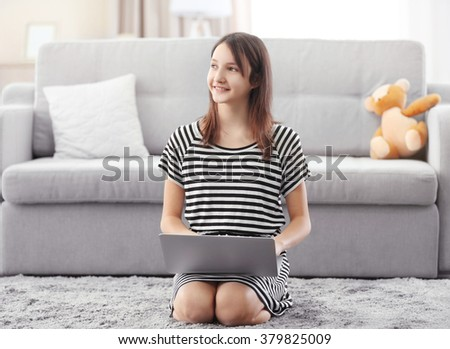Beautiful girl with laptop on grey carpet indoor - stock photo