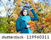 Beautiful girl with leaves on an sunny autumn-day in park - stock photo