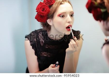 Beautiful girl with lipstick watching in mirror - stock photo