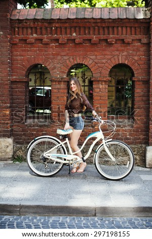 Beautiful girl with long blond hair wearing on dark blouse and blue shorts posing with bicycle on the brick wall background, on the old city street - stock photo