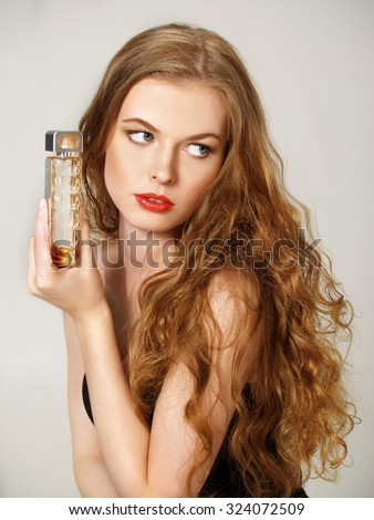 Beautiful  girl with long blonde hair holds bottle of perfume