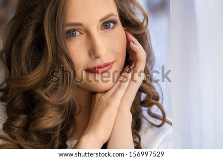 Beautiful girl with long curly hair holds her hands near her face - stock photo