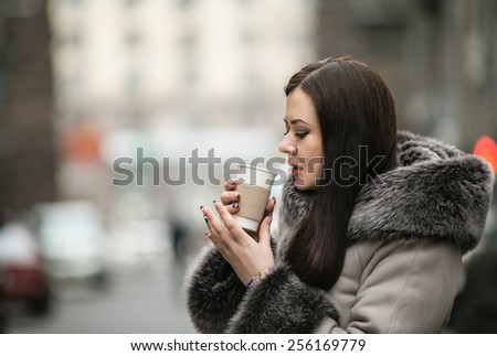 Beautiful girl with long dark hair on the background of a winter landscape of urban drinking hot coffee from a paper cup - stock photo